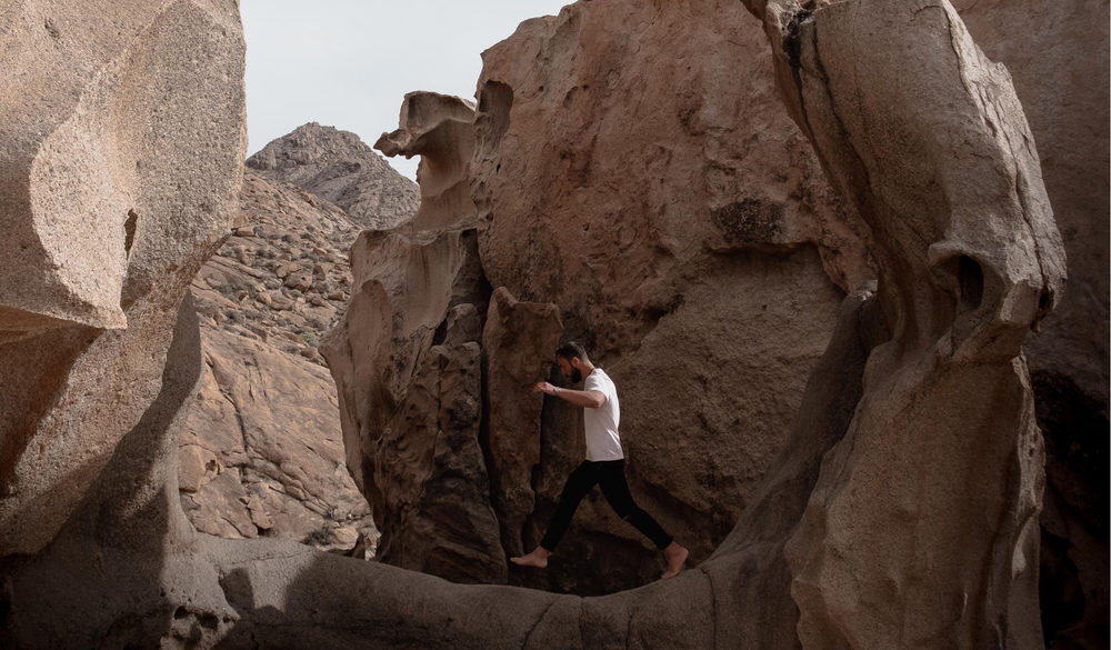 A man walking on a rock in a canyon